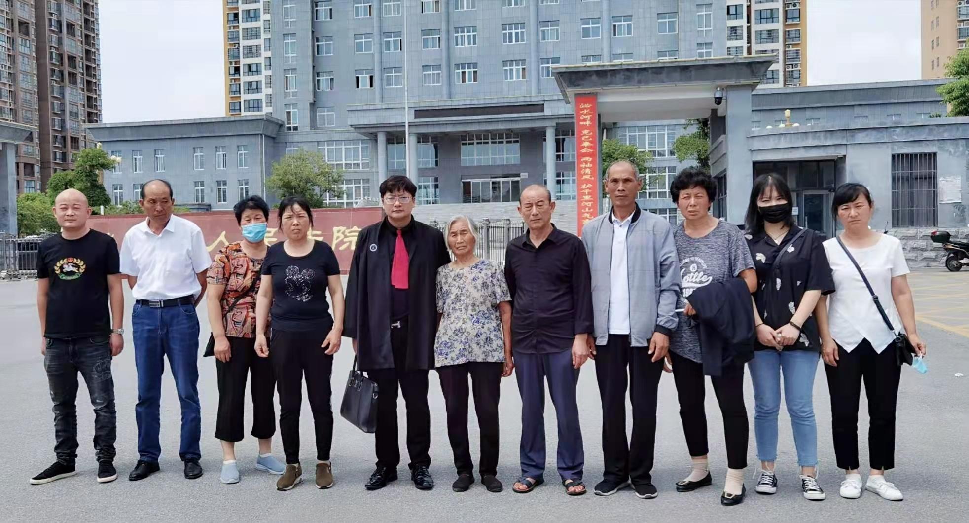 2020年8月,周兆成律师与被害人家属在泌阳县人民法院门口合照。受访者供图