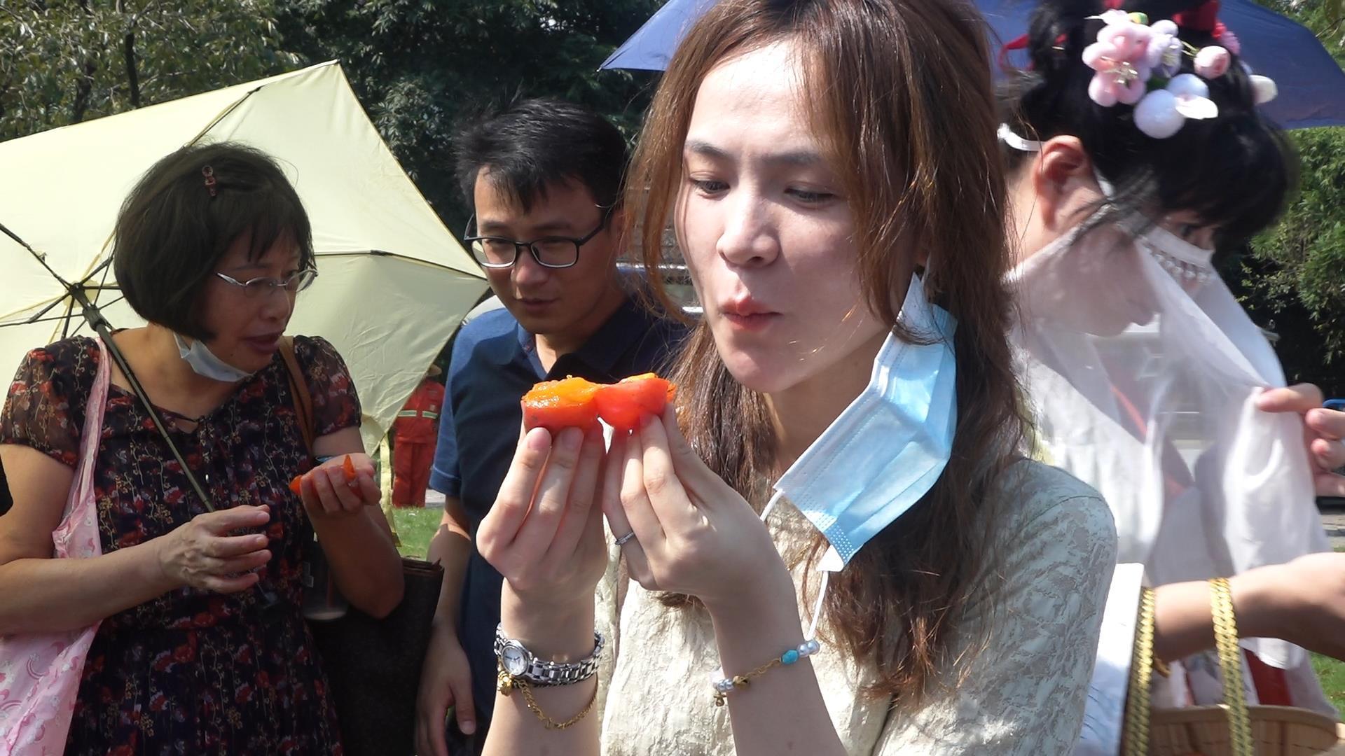 游客们在现场品尝火柿 尚天宇 摄