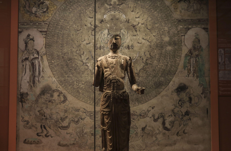 木雕八臂观音残像,背后是复制的莫高窟第3窟千手千眼观音壁画。新京报记者 浦峰 摄