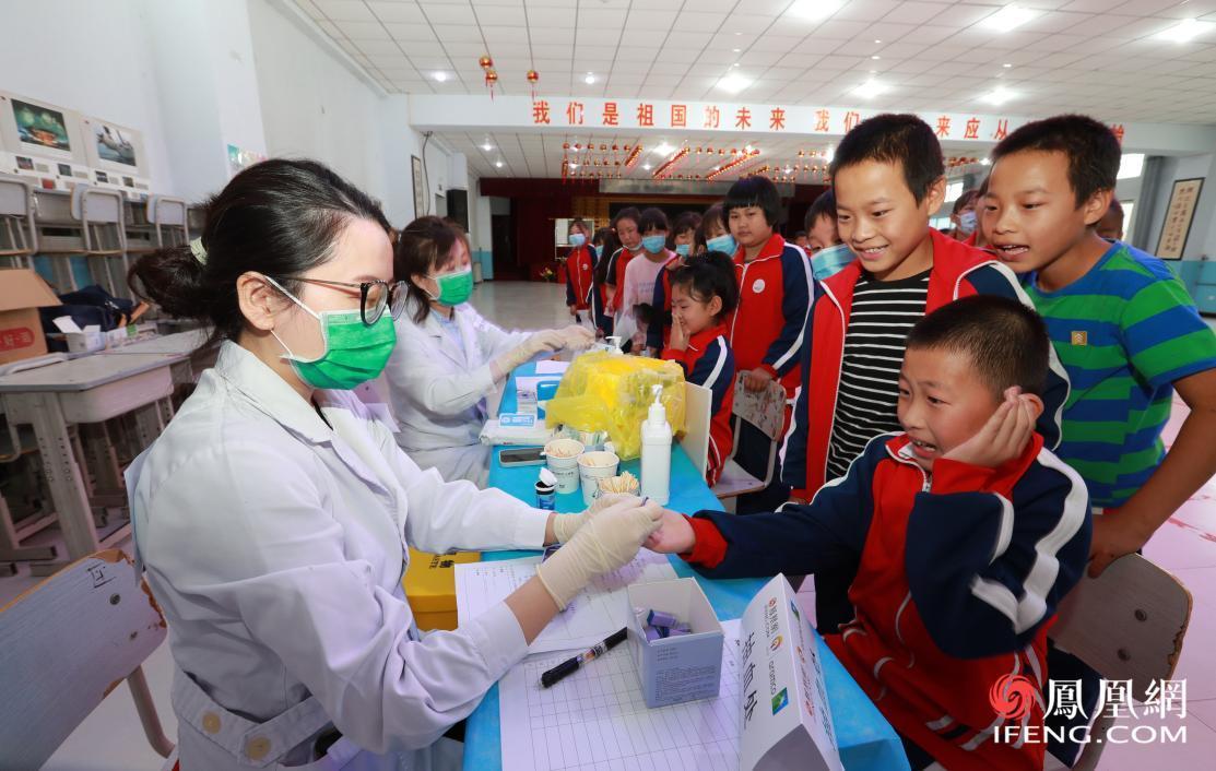 志愿者为孩子进行血红蛋白检测