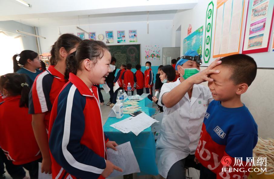 志愿者为孩子进行耳鼻喉科检查
