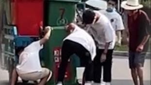 """保洁大爷的垃圾桶从车上掉落 路过男生合力将其""""归位"""""""