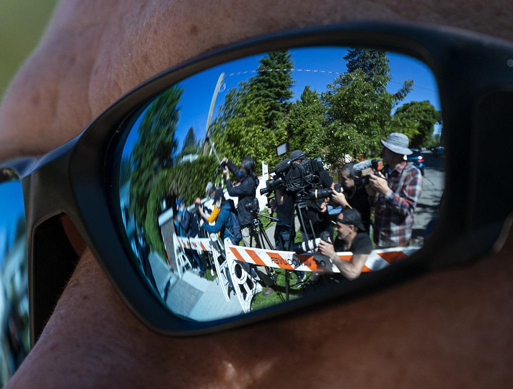 当地时间2020年5月27日,加拿大温哥华,孟晚舟离开家,前往加拿大不列颠哥伦比亚省高等法院。图为在一名保安的墨镜倒影中看到孟晚舟家旁的媒体人群。