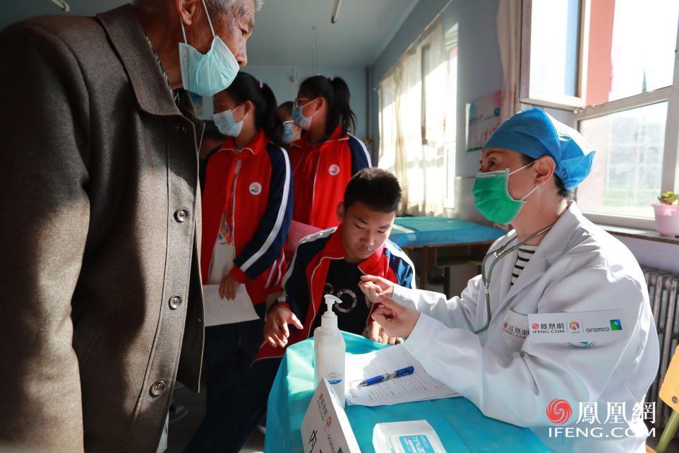 志愿者为孩子进行内科检查