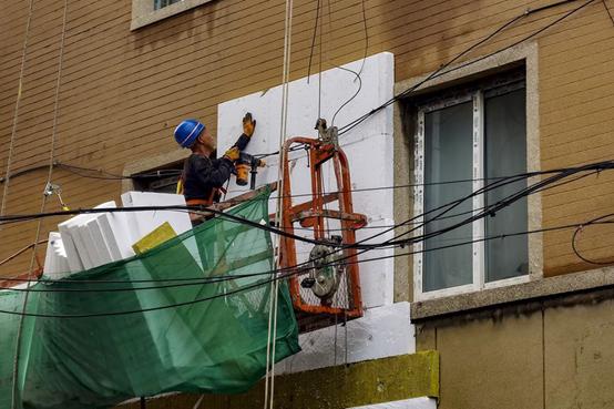 2021年8月29,辽宁省锦州市上海路东段的一栋老旧住宅楼正在进行加装外墙保温材料。图|IC photo