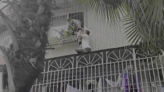 男孩头卡3楼护栏窗外悬空 退伍军人跪地托举等消防救援