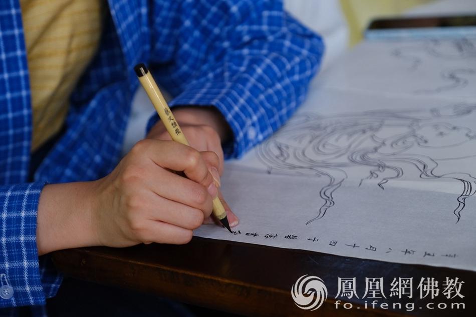 游客在自己临摹的白描线稿上书写名字(图片来源:凤凰网佛教 摄影:于椿根)