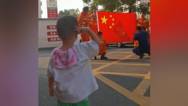 消防员外出拍摄,偶遇萌娃对着国旗敬礼