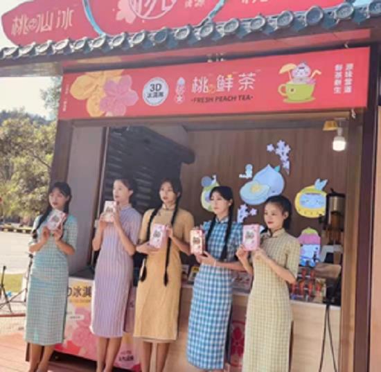桃花小妹在桃鲜茶摊位前展示文创产品