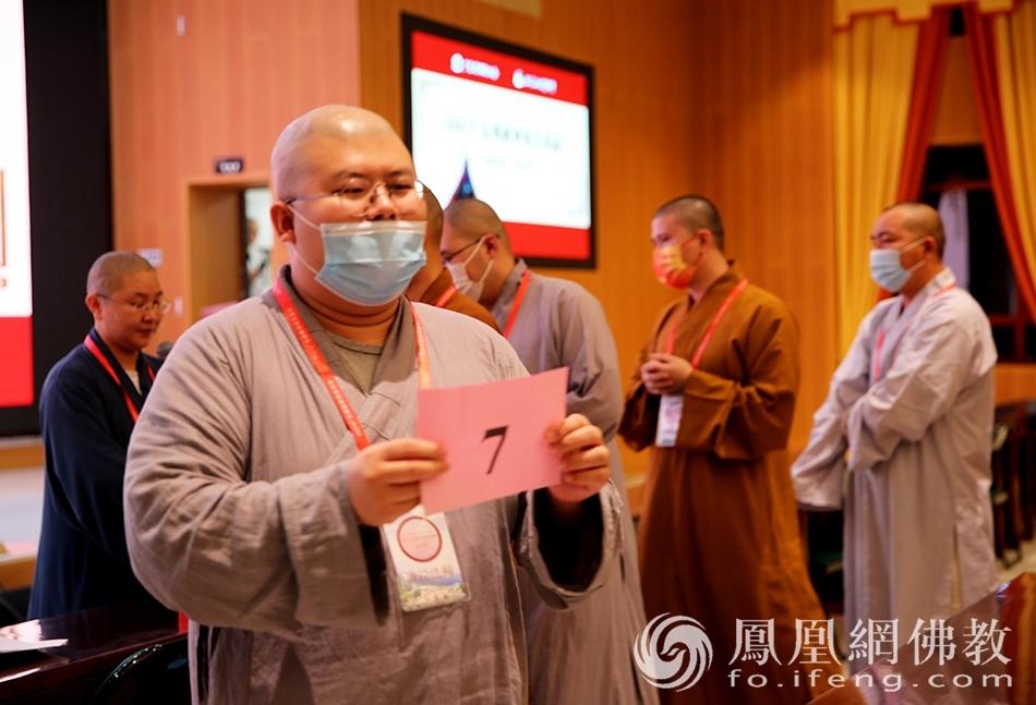 参赛法师展示自己抽到的签号(图片来源:凤凰网佛教 摄影:李保华)