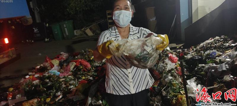 环卫工人在垃圾堆内找居民遗失的财物。(海口市园林环卫局供图)