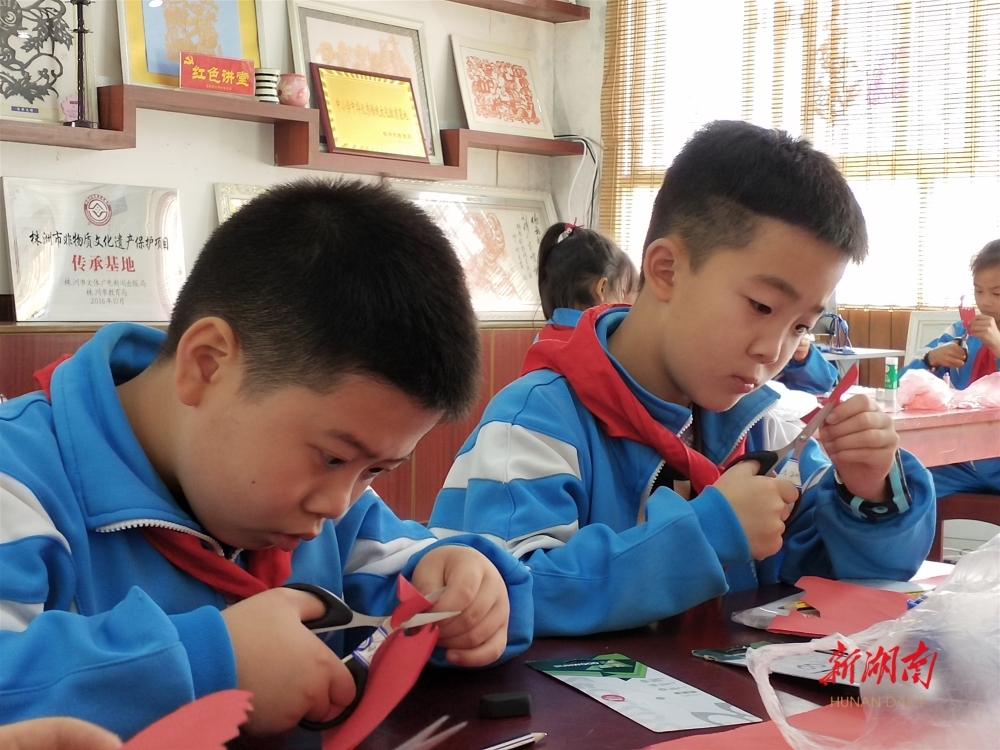 ▲ 金轮侨心学校的学生正在进行剪纸创作。